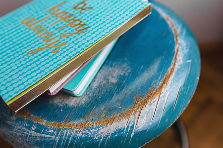 Blue notebooks and a camera on a blue wooden stool