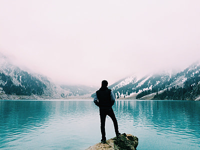 man standing near large body of water