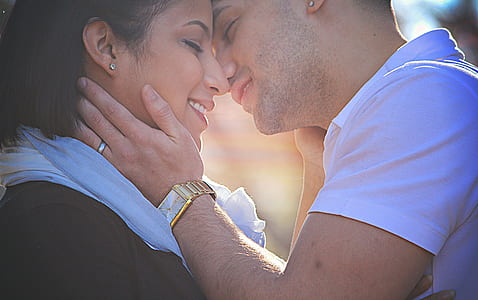 man and woman about to kiss during daytime