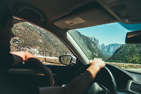 man wearing black shirt driving car