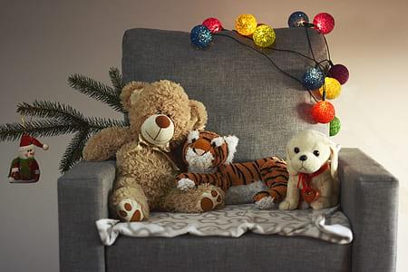 brown bear, tiger, and dog plush toys on black sofa chair