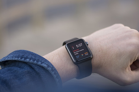 person wearing space gray case black sport band Apple Watch at 5:07
