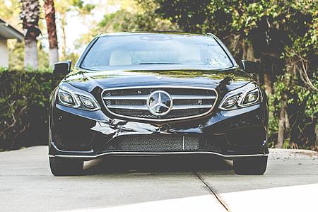 black Mercedes-Benz car on gray concrete road