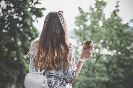 selective focus photograph of woman holding cup