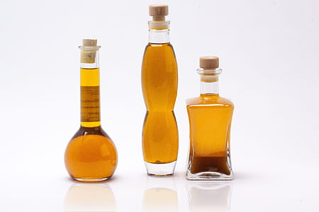 three olive oils on clear glass bottles
