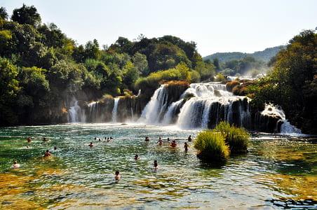 People Swimming Near Waterfall during Daytime