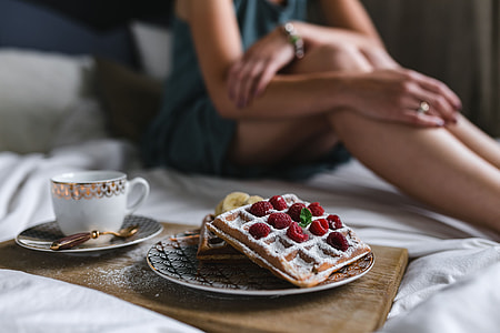 Breakfast in bed - waffles with raspberries and cup of coffee on the tray