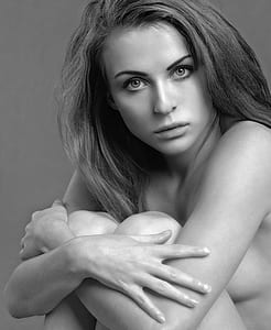 grayscale photo of sitting topless woman