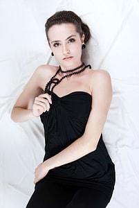 woman wearing black sweetheart-neckline dress