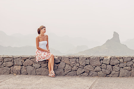 woman in white sleeveless dress sitting in stone bench