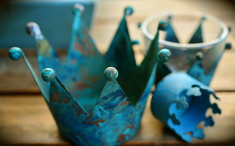 selective focus photo of three teal metal crowns on brown wooden surface