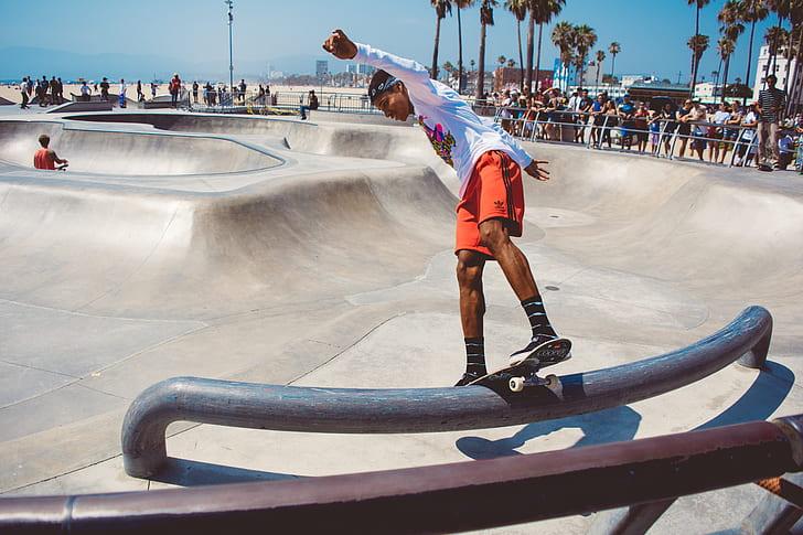 man wearing white long-sleeved shirt ride-on skateboard grinding on rail photography