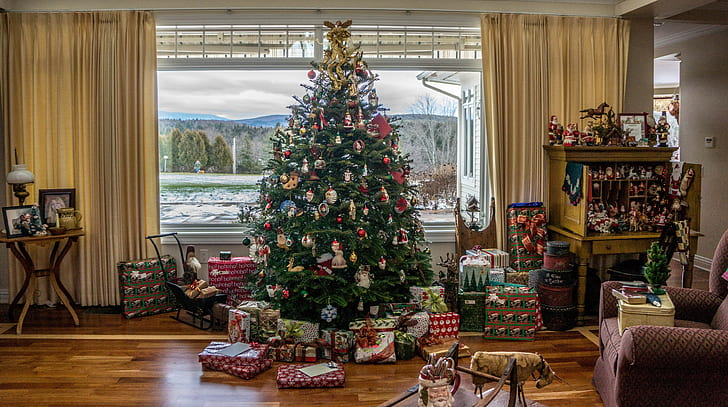 green Christmas Tree with gift boxes near glass window during daytime