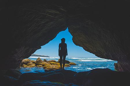 silhouette of woman standing on rock beside ocean