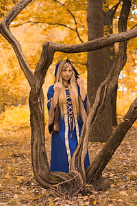 woman wearing blue and gold dress standing beside tree