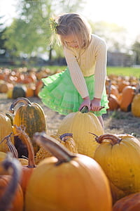 girl in white sweatshirt holding a yellow pumpkin during daytime