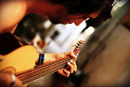 photo of person playing acoustic guitar
