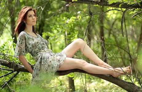 woman wearing green floral mini dress on tree branch