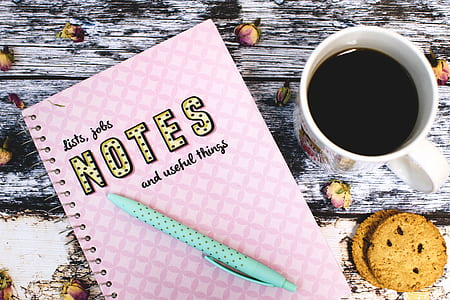 pink Notes with teal click pen next to white ceramic mug with coffee