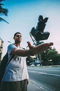 Man Throwing Black Camera in Air