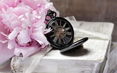 black skeleton pocket watch beside pink petaled flower