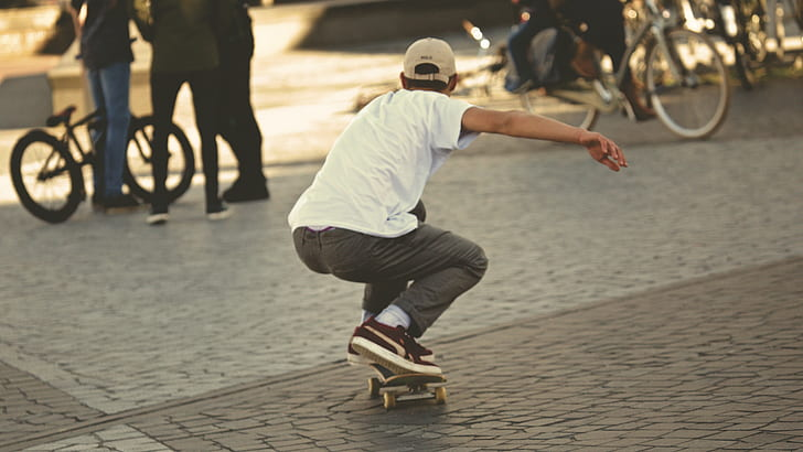 Man in White Shirt and Brown Jeans Riding Skateboard