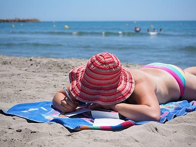 woman wearing bikini lying on textile holding pen
