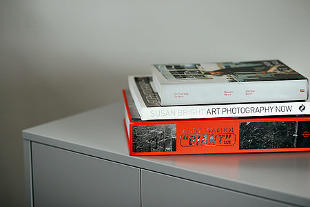 three assorted books on gray side board