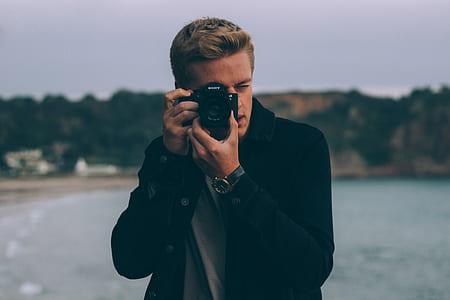 man in black blazer using DSLR camera