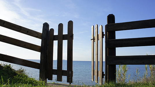 brown wooden gate opened near seashore at daytime