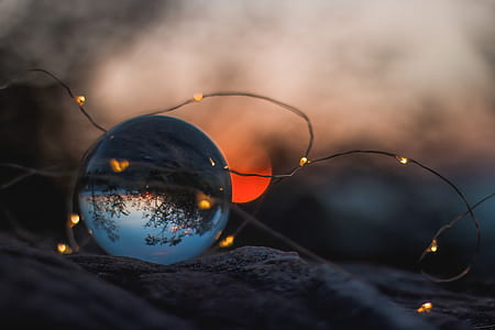 selective focus photography of brown string light and glass ball paperweight during sunset photo