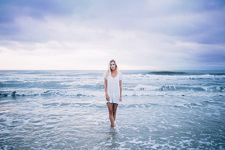 woman with white hair in white dress standing on seashore
