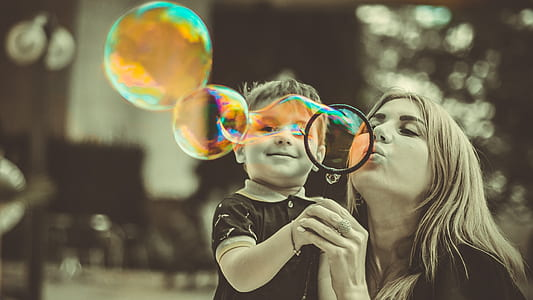 woman wearing black top with her child playing with bubbles
