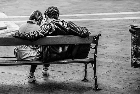 grayscale photo of male and female sitting at bench