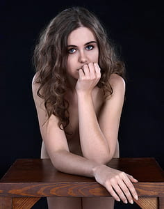 naked woman leaning on the table