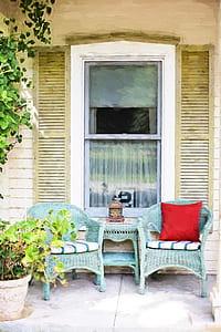 two green wicker armchairs near sash window