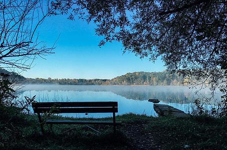 photo of bench near a lake under blue sky