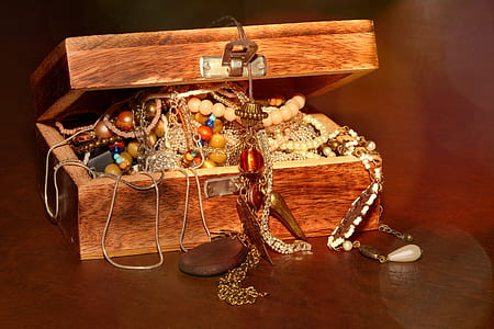 brown wooden box with necklaces and bracelets inside