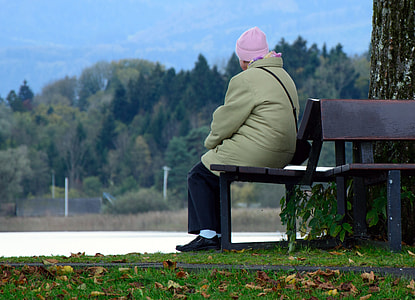 person wearing green coat seating on brown wooden bench