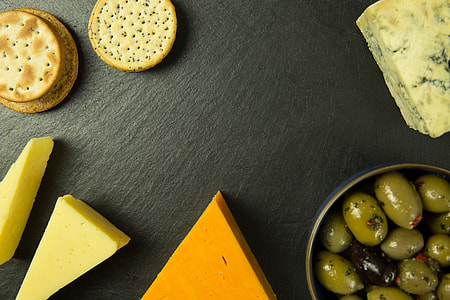 Overhead shot of cheese, olives and biscuits on a slate board