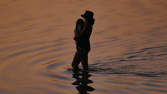 silhouette of a woman at body of water