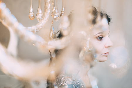 selective focus photography of woman behind chandelier