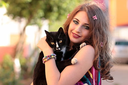 woman holding tuxedo cat
