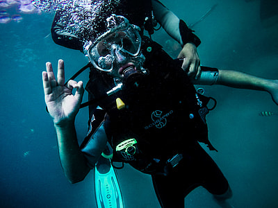 person wearing scuba suit under water