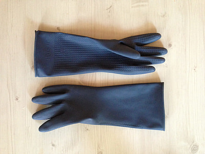 pair of black rubber gloves on beige wooden surface