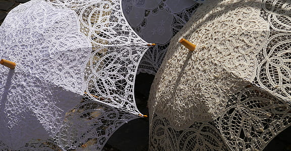 photo of two beige and white lace umbrellas