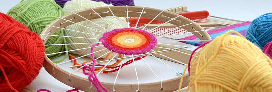 round brown wooden frame with assorted-color threads and yarns