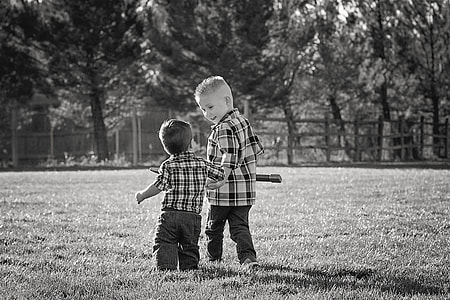 gray scale photography of two children walking through the field during daytime