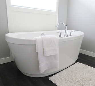white enamel bathtub with towel