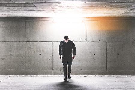 Young Man Walking in Conrete Underground Walkway